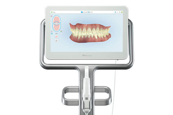 White panoramic dental x ray machine with small side monitor displaying an x ray and treatment information