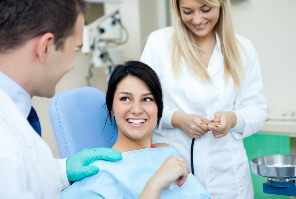 A young women sitting in the dental chair with her dentists standing next to her.
