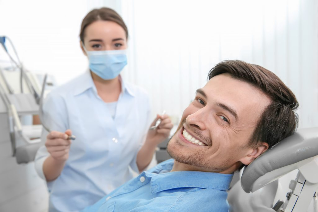 A man sitting in a dental chair smiling with a dentist behind him